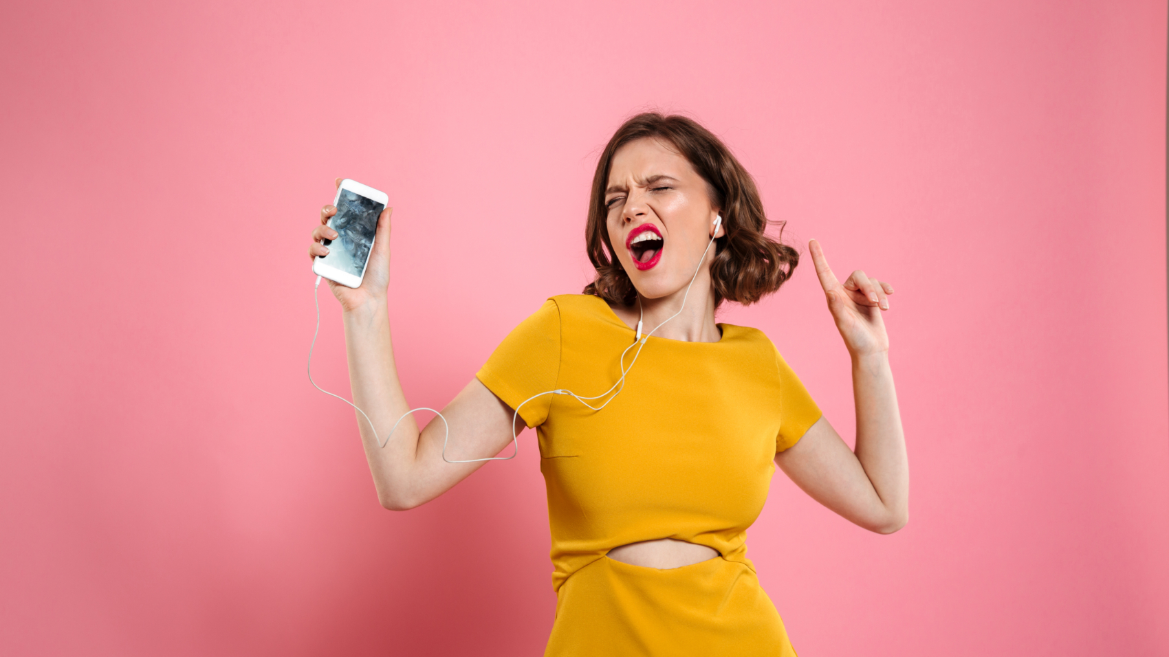 Portrait of a joyful woman in dress and make up listening to music with earphones while holding mobile phone and singing isolated over pink background